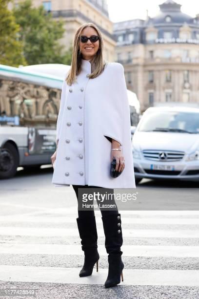 Guest wearing white poncho coat outside Balmain during Paris Fashion Week - Womenswear Spring Summer 2020 on September 27, 2019 in Paris, France.
