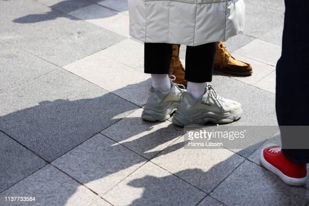 Guest wearing white puffer coat and Balenciaga sneakers is seen at the Hera Seoul Fashion Week 2019 F/W at Dongdaemun Design Plaza at Dongdaemun...
