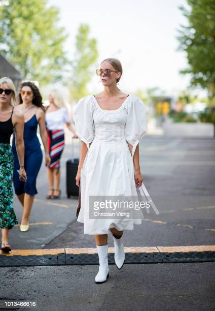 A guest wearing white ruffled dress is seen outside MUF10 during the Copenhagen Fashion Week Spring/Summer 2019 on August 8 2018 in Copenhagen Denmark