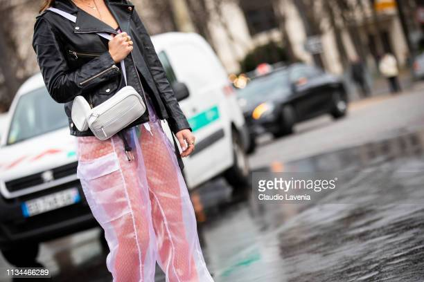 A guest wearing white sheer pants black leather jacket and white bag is seen outside Chanel on Day 9 Paris Fashion Week Autumn/Winter 2019/20 on...