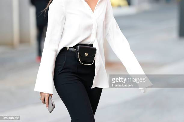 A guest wearing white shirt and bumbag during MercedesBenz Fashion Week Resort 19 Collections at Carriageworks on May 17 2018 in Sydney Australia