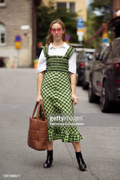 Guest wearing white shirt with checked light green dress and brown bag outside Iggy Jeans during Stockholm fashion week Spring/Summer 2022 on...