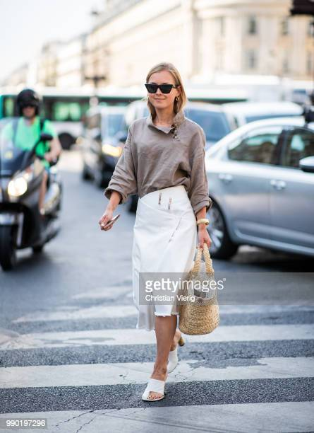 A guest wearing white skirt straw bag white sandals is seen outside Schiaparelli on day two during Paris Fashion Week Haute Couture FW18 on July 2...