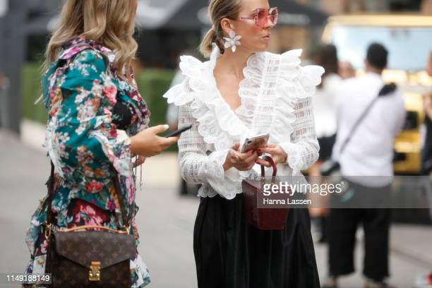 A guest wearing white top and floral earrings at MercedesBenz Fashion Week Resort 20 Collections on May 15 2019 in Sydney Australia