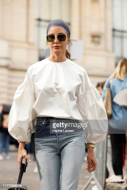 A guest wearing white top and jeans outside the Elie Saab show during Womenswear Spring/Summer 2020 show Paris Fashion Week on September 28 2019 in...