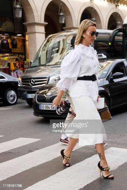 A guest wearing white top and skirt and Louis Vuitton bag outside Giambattista Valli during Paris Fashion Week Womenswear Spring Summer 2020 on...