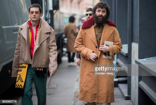 A guest wearing yellow black football scarf beige jacket red track suit jacket and a guest wearing beige coat is seen outside No21 during Milan Men's...