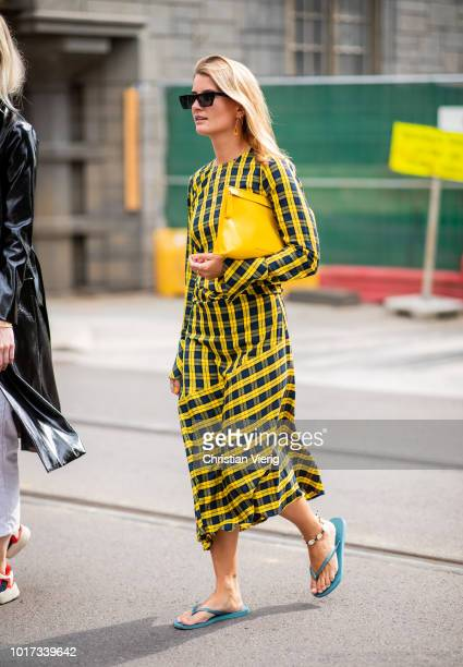 A guest wearing yellow clutch and checked dress seen outside Pia Tjelta during Oslo Runway SS19 on August 15 2018 in Oslo Norway