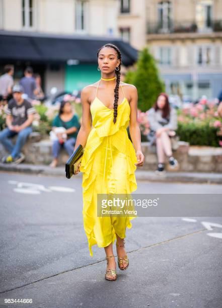 A guest wearing yellow dress is seen outside Kenzo on day six of Paris Fashion Week Menswear SS19 on June 24 2018 in Paris France