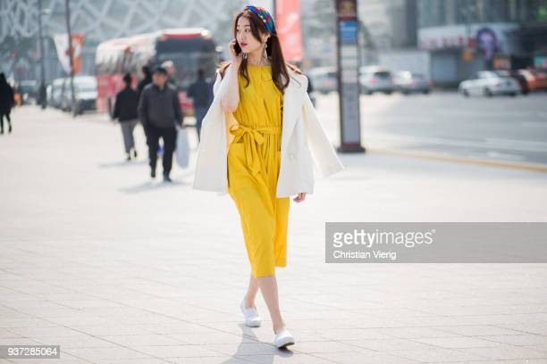 A guest wearing yellow dress scarf in her hair white jacket over her shoulders while doing a phone call with her smartphone is seen at the Hera Seoul...