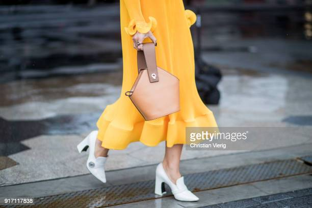A guest wearing yellow dress seen outside Tibi on February 11 2018 in New York City