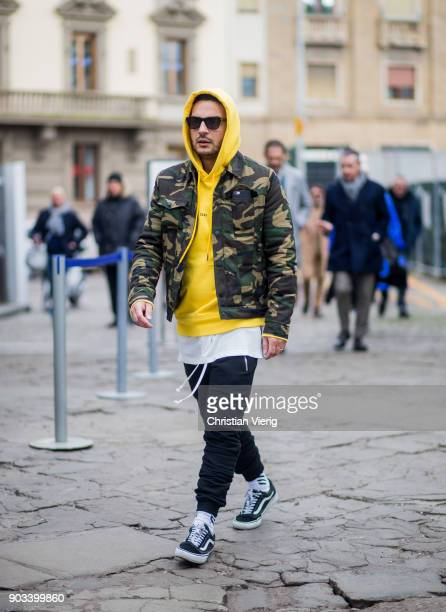 A guest wearing yellow hoody camouflage jacket track suit pants Vans is seen during the 93 Pitti Immagine Uomo at Fortezza Da Basso on January 10...