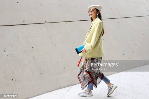 Guest wearing yellow jacket, scarf skirt and jeans and Yeezy Boost sneakers is seen at the Hera Seoul Fashion Week 2019 F/W at Dongdaemun Design...