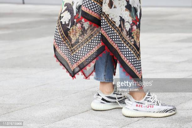 Guest wearing yellow jacket scarf skirt and jeans and Yeezy Boost sneakers is seen at the Hera Seoul Fashion Week 2019 F/W at Dongdaemun Design Plaza...