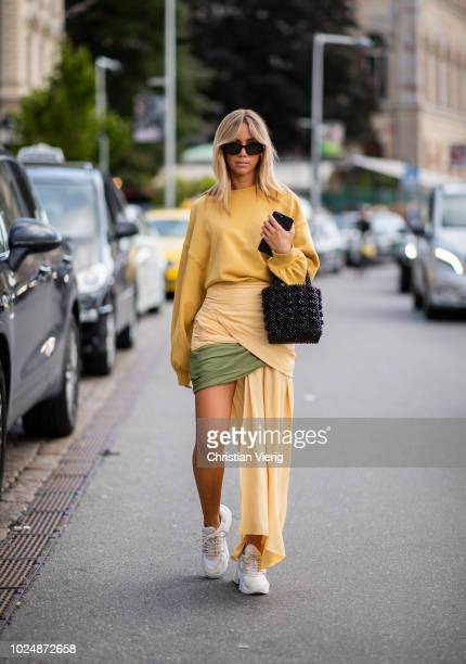 A guest wearing yellow knit and asymmetrical skirt is seen during Stockholm Runway SS19 on August 28 2018 in Stockholm Sweden