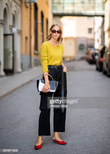A guest wearing yellow knit high waist cropped black pants red shoes white black bag seen during Stockholm Runway SS19 on August 28 2018 in Stockholm...