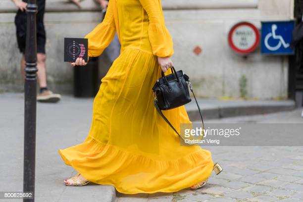 A guest wearing yellow maxi dress black Phillip Lim bag outside Dior Homme during Paris Fashion Week Menswear Spring/Summer 2018 Day Four on June 24...