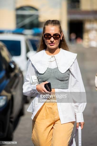 Guest wearing yellow trousers, white blouse, grey bustier is seen outside Samsøe & Samsøe during Copenhagen Fashion Week Spring/Summer 2021 on August...