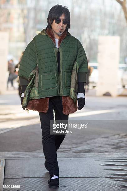 A guest wears a 3/4 sleeve length cropped green camouflage and solid puffer jacket with pockets over a fur jacket during Milan Men's Fashion Week...