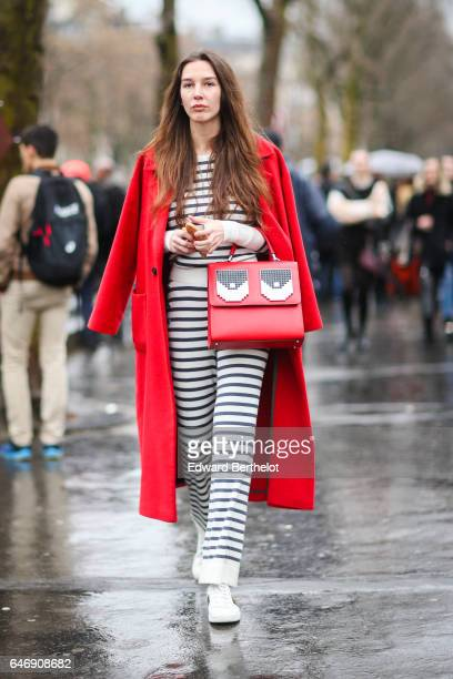 A guest wears a a red coat striped pants a striped top and a red bag with printed eyes outside the Rochas show during Paris Fashion Week Womenswear...