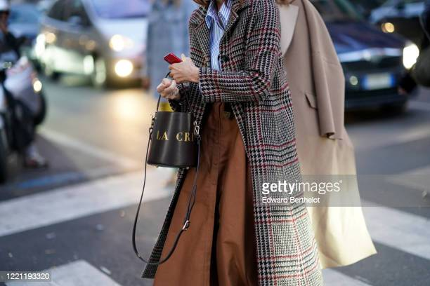 Guest wears a bag, a brown skirt, a houndstooth pattern coat, outside N°21, during Milan Fashion Week Fall/Winter 2020-2021 on February 19, 2020 in...