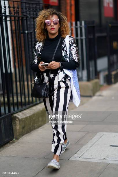 A guest wears a bag striped pants outside JW Anderson during London Fashion Week September 2017 on September 16 2017 in London England