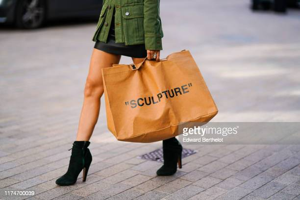 A guest wears a bag with the word sculpture during London Fashion Week September 2019 on September 14 2019 in London England