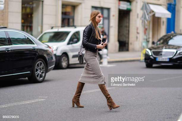 A guest wears a balck leather jacket a gray skirt brown suede boots during Paris Fashion Week Womenswear Fall/Winter 2018/2019 on March 5 2018 in...