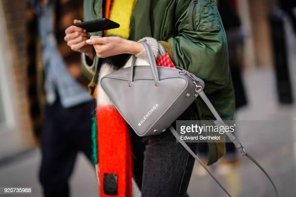 A guest wears a Balenciaga triangular bag during London Fashion Week February 2018 on February 17 2018 in London England