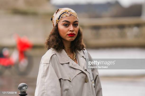 Guest wears a bandanna, a gray trench coat, a golden necklace, outside Chloe, during Paris Fashion Week - Womenswear Fall/Winter 2020/2021, on...