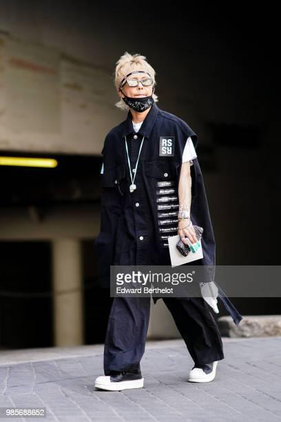 A guest wears a bandanna an black oversized shirt flared pants outside 1017 ALYX 9SM during Paris Fashion Week Menswear SpringSummer 2019 on June 24...