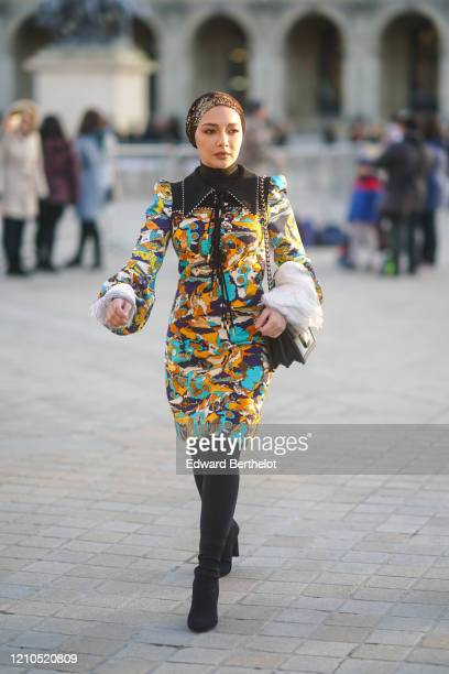 Guest wears a bandanna over the head, a multicolor dress with printed patterns, a Vuitton bag, thigh high boots, outside Vuitton, during Paris...