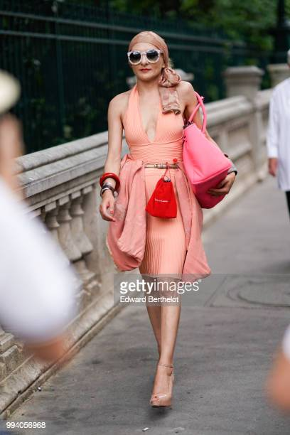 A guest wears a bandanna sunglasses a pink dress with low neck a red mini bag on the belt a pink large bag nunde colored shoes outside JeanPaul...