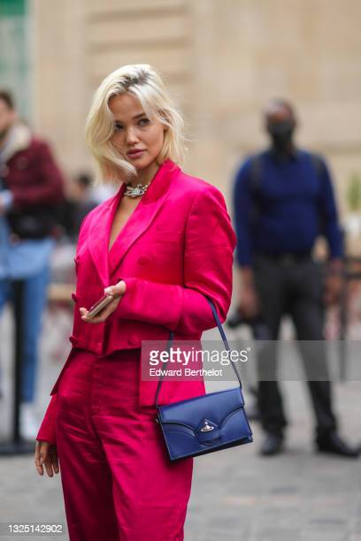 Guest wears a beaded pearl bejeweled necklace, black bras a neon pink / fuchsia lustrous silky / shiny blazer jacket, matching flared slit pants, a...