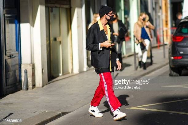 Guest wears a beanie hat, a black blazer jacket with yellow lapels, red Adidas striped sport pants, sneakers shoes, glasses, outside Paco Rabanne,...