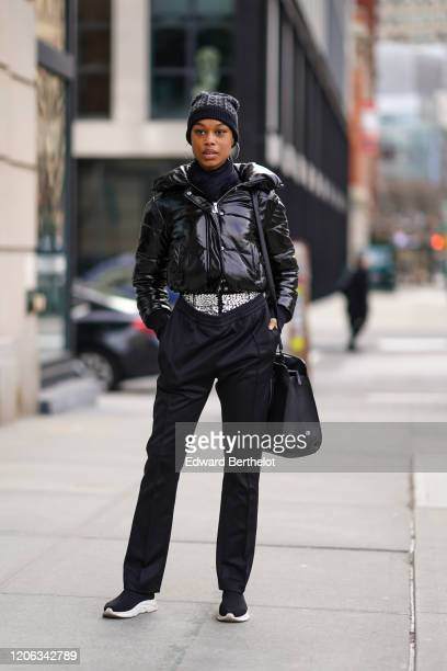 A guest wears a beanie hat a black turtleneck pullover a black shiny puffer coat black pants a bag sneakers during New York Fashion Week Fall Winter...