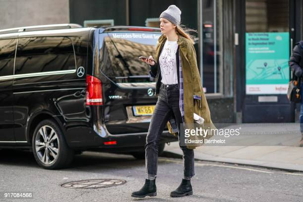 A guest wears a beanie hat a green khaki coat black pants black shoes during London Fashion Week Men's January 2018 at on January 6 2018 in London...
