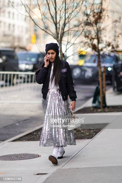A guest wears a beanie hat a silver shiny glittering pleated skirt a white bag shoes a Vans black jacket during New York Fashion Week Fall Winter...