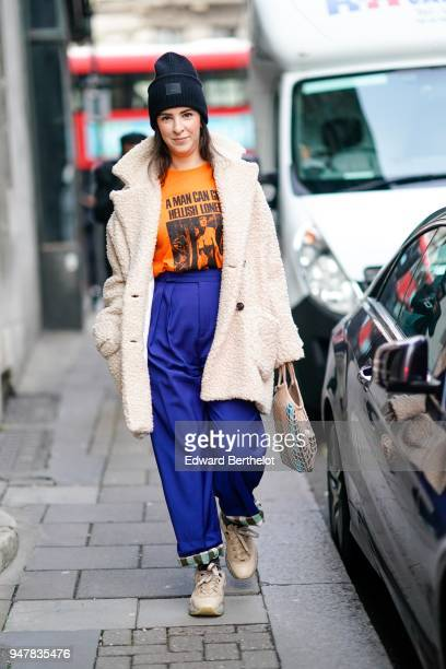 A guest wears a beanie hat a white coat an orange tshirt blue pants brown shoes during London Fashion Week Men's January 2018 at on January 6 2018 in...