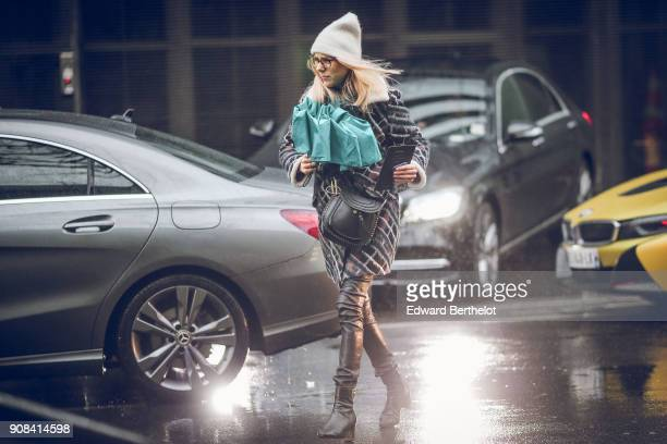 A guest wears a beanie hat an umbrella a bag black leather boots a coat in front of car lights under the rain outside Paul Smith during Paris Fashion...