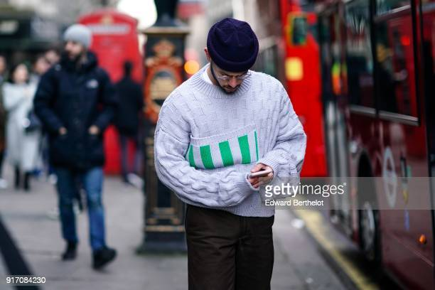 A guest wears a beanie hat glasses a gray wool pull over during London Fashion Week Men's January 2018 at on January 6 2018 in London England