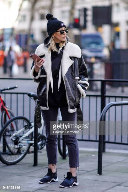 Guest wears a beanie hat with a pompom, an aviator jacket, cropped pants, sneakers shoes, during London Fashion Week February 2018 on February 16,...