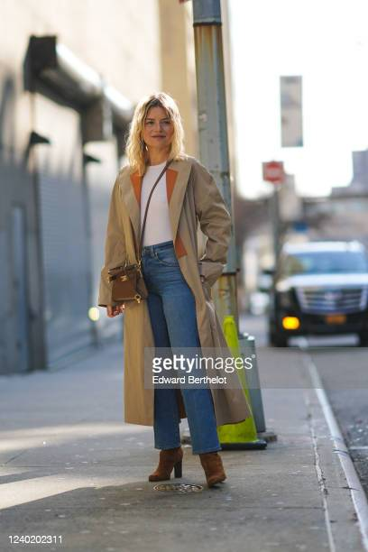 Guest wears a beige and brown trench coat, a white t-shirt, blue jeans, a brown leather bag, brown suede boots, outside Tory Burch, during New York...
