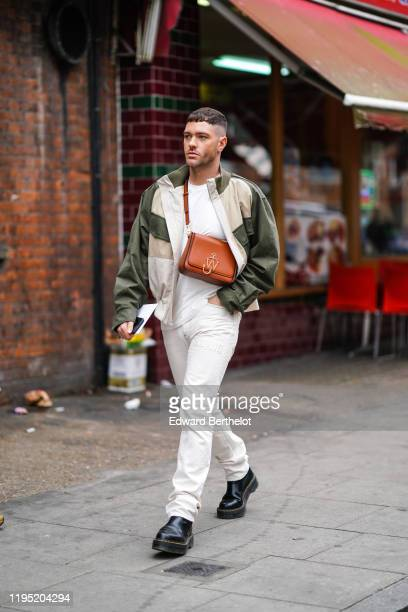 Guest wears a beige and green jacket, a JW Anderson brown leather bag, a white t-shirt, pants, black leather shoes, outside JW Anderson, during...