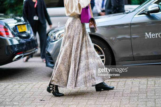 Guest wears a beige and grey python pattern long skirt, a brown Gucci bag, black pointy boots with buckles, during London Fashion Week September 2019...
