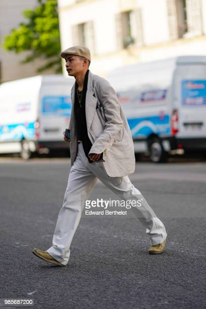 A guest wears a beige beret a white jacket white pants shoes outside 1017 ALYX 9SM during Paris Fashion Week Menswear SpringSummer 2019 on June 24...