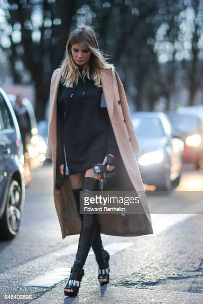 A guest wears a beige coat a black dress and black leather thigh high boots outside the Galliano show during Paris Fashion Week Womenswear...