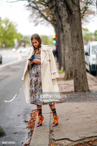 A guest wears a beige coat a flower print dress flower print shoes outside John Galliano during Paris Fashion Week Womenswear Spring/Summer 2018 on...