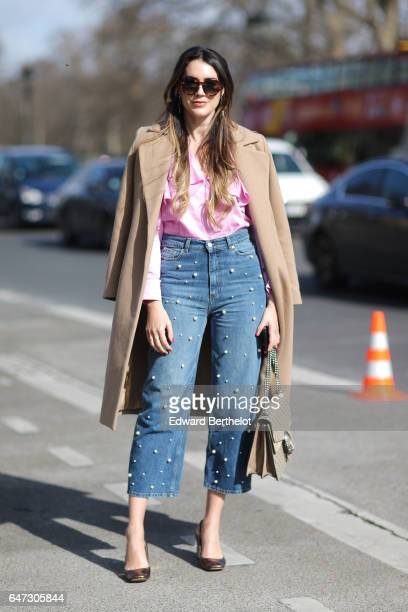 A guest wears a beige coat a pink top and blue denim jeans outside the Manish Arora show during Paris Fashion Week Womenswear Fall/Winter 2017/2018...