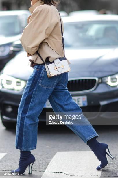 A guest wears a beige coat a Prada bag blue jeans and blue heels outside the Miu Miu show during Paris Fashion Week Womenswear Fall/Winter 2017/2018...